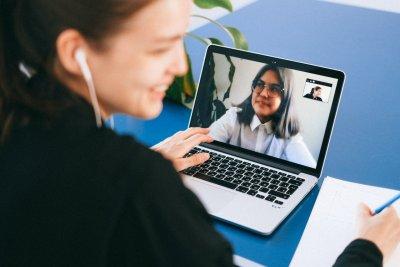 Junge Frau vor einem Laptop mit laufendem Videogespräch
