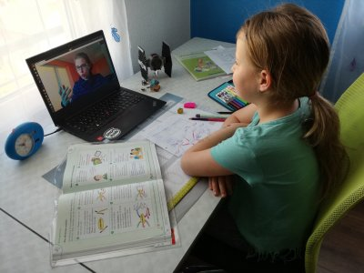 Schoolgirl in front of laptop and school materials