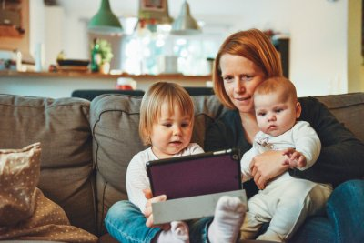 Mutter mit Kleinkindern und Tablet auf der Couch.