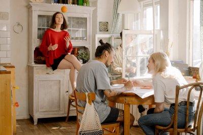 Eine Gruppe Studierender sitzen um einen Küchentisch herum.
