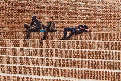 Jugendliche sitzen auf einer Treppe und nutzen ihre Mobilgeräte