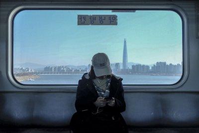 Mädchen in U-Bahn mit Ausblick auf Gangnam im Hintergrund