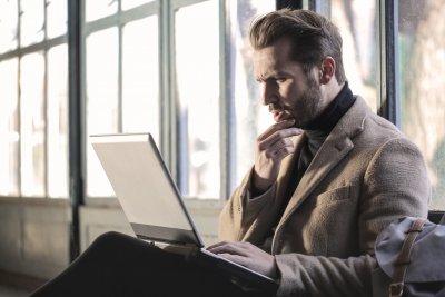 Ein Mann schaut verwirrt auf seinen Laptop.