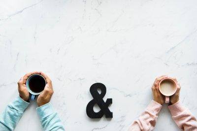 Zwei Menschen, die Kaffeetassen in der Hand halten