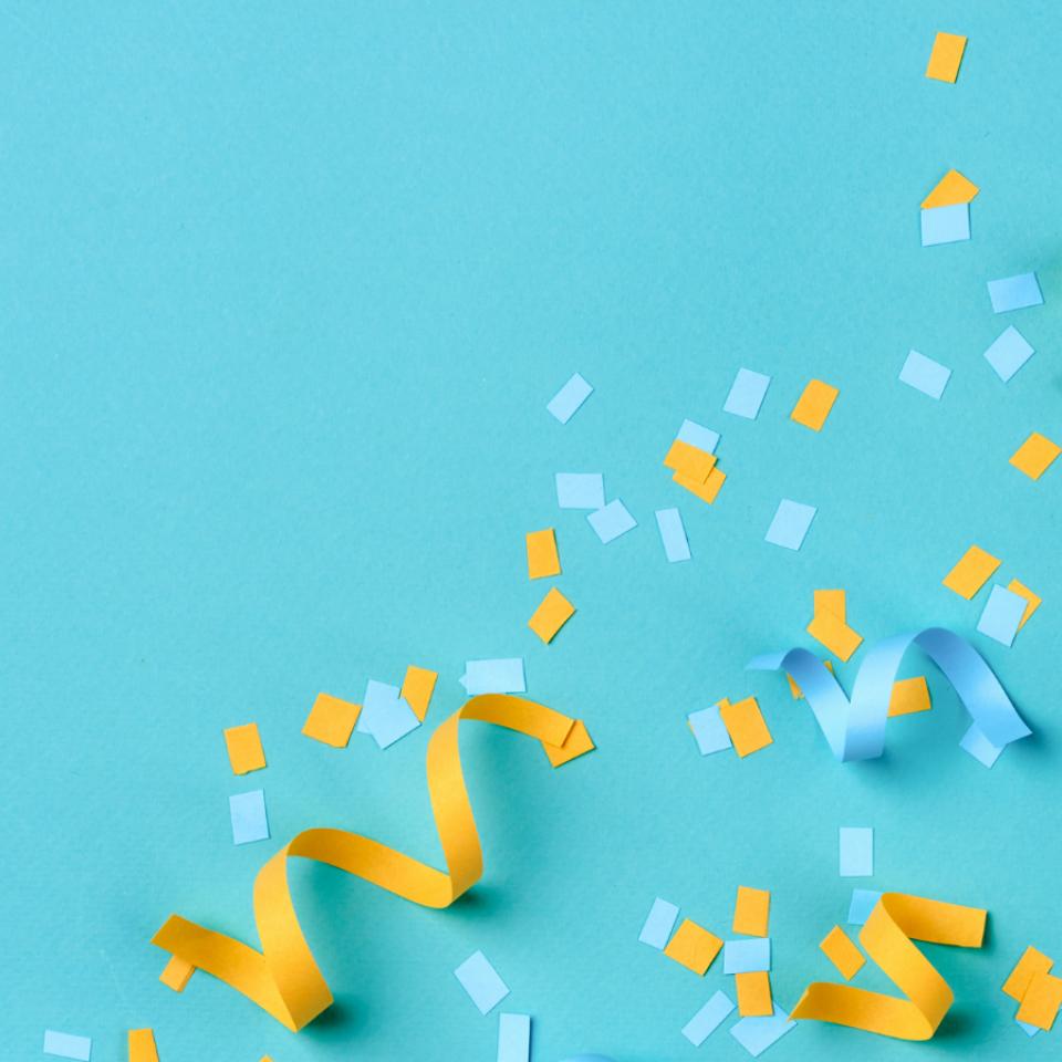 gelbe und blaue Luftschlangen und Konfetti auf türkisem Grund